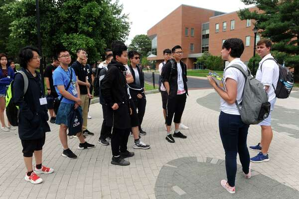 Alexandra Ose, a sophomore from Vernon, and Peter Purcell, and junior for Cheshire, leads a tour for entering international students on the University of Connecticut campus, in Storrs, Conn. Aug. 20, 2018.