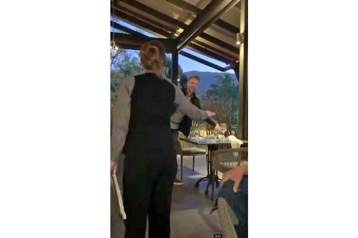 A screengrab from a video posted by @jordanlizchan to social media showing a Lucia Restaurant & Bar server, left, ordering a customer, right, to leave the restaurant after they made racist, anti-Asian comments to other patrons.