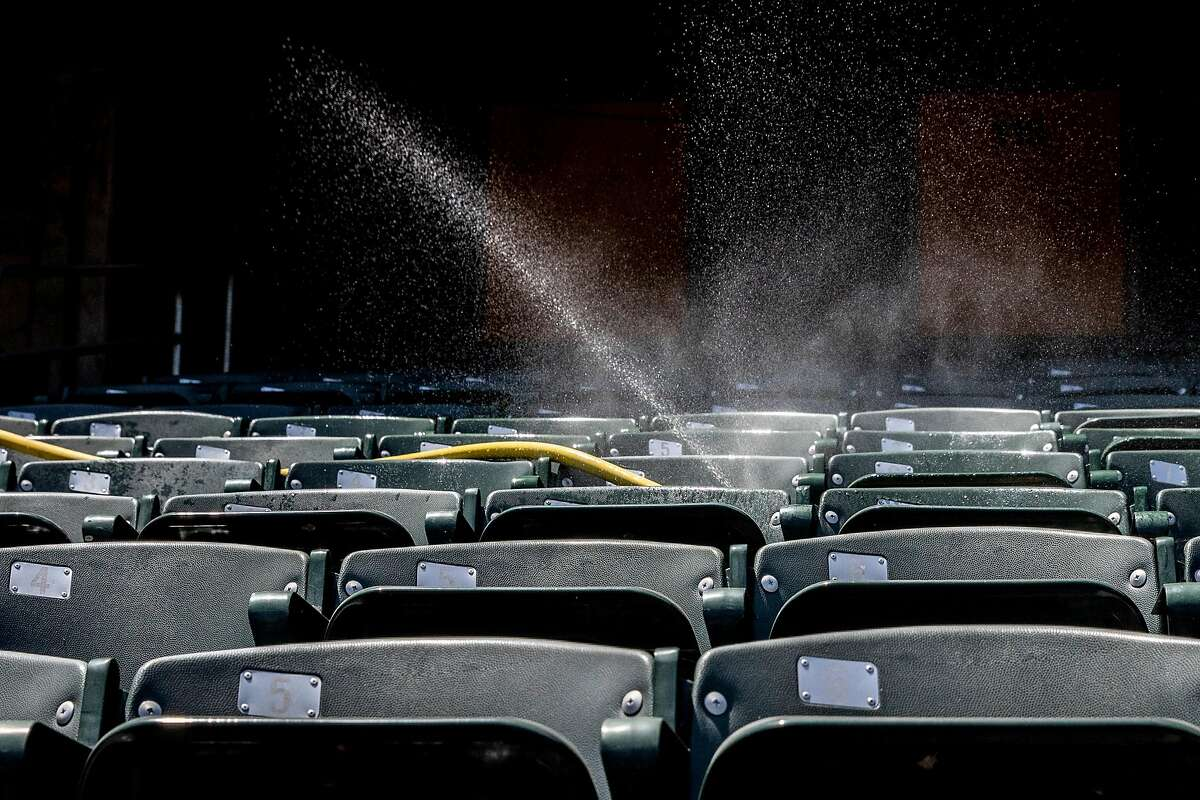 Water mists empty sadium seats during an Oakland A's training camp workout at O.Co Coliseum in Oakland, Calif. Tuesday, July 7, 2020. Due to COVID-19, the 2020 MLB season has been postponed with players just beginning to return for warmups and practices while wearing masks and keeping social distance.