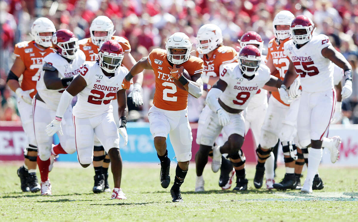 Texas quarterback Roschon Johnson (2) runs up the field for a big play as the Oklahoma defense gives chase during the second half in the Red River Showdown at the Cotton Bowl in Dallas on Saturday, Oct. 12, 2019. Oklahoma won, 34-27.