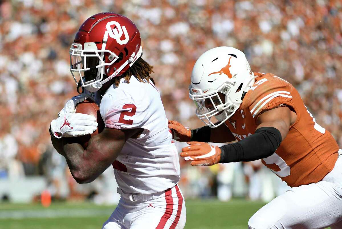 Oklahoma wide receiver CeeDee Lamb (2) secures a touchdown reception in front of Texas defensive back Brandon Jones (19) during the first half of an NCAA college football game at the Cotton Bowl, Saturday, Oct. 12, 2019, in Dallas. (AP Photo/Jeffrey McWhorter)
