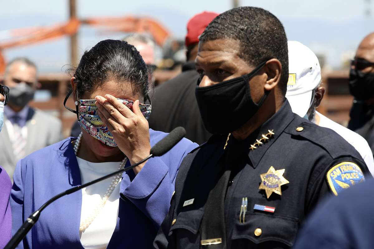 """San Francisco Mayor London Breed uses her face mask to wipe tears as San Francisco Police Chief William Scott speaks during a press conference - regarding the death of Jace Young - at Agua Vista Park in San Francisco, Calif., on Tuesday, July 7, 2020. Young, 6, was fatally shot during an Independence Day celebration. """"We have to be outraged every time there's a death in our community. Jace was innocent,"""" Breed said. """"Accountability starts with us."""""""