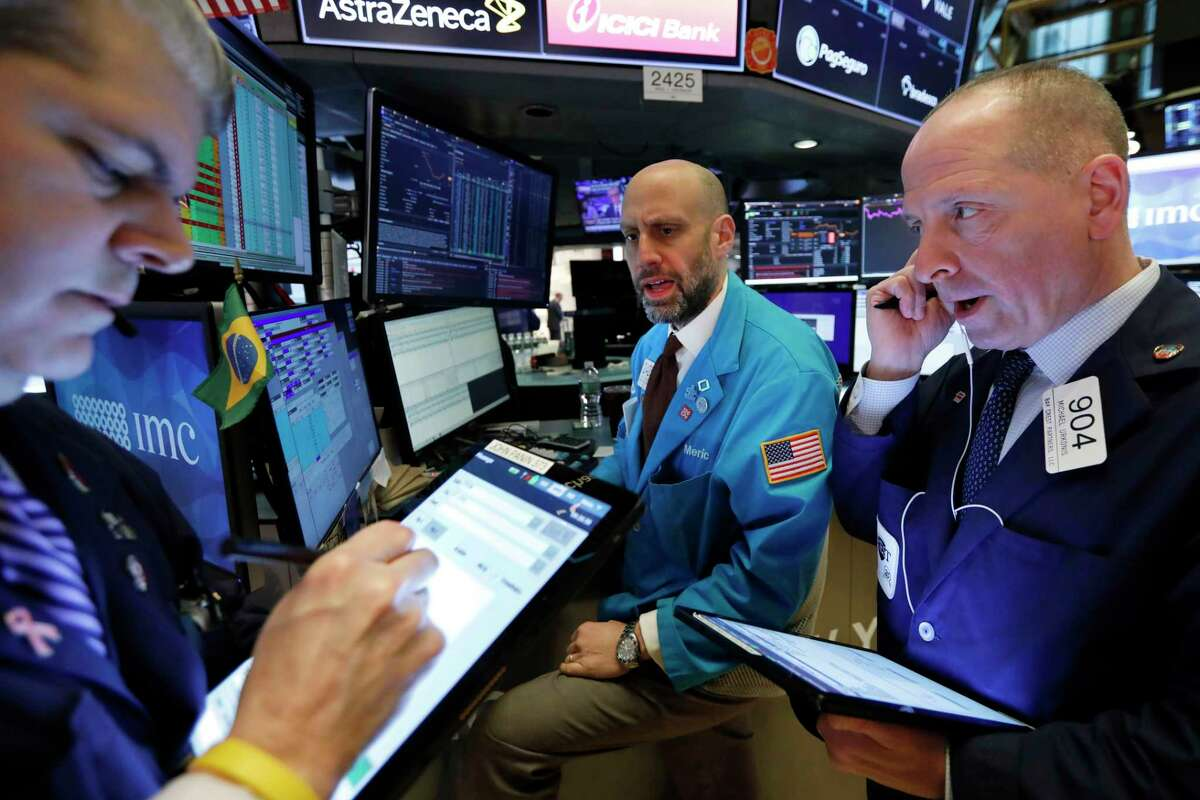 FILE - In this March 12, 2020, file photo, specialist Meric Greenbaum, center, works with traders on the floor of the New York Stock Exchange. U.S. stocks are dipping modestly in early trading Tuesday, July 7, 2020, as expanding coronavirus outbreaks dim hopes for a speedy recovery. (AP Photo/Richard Drew, File)