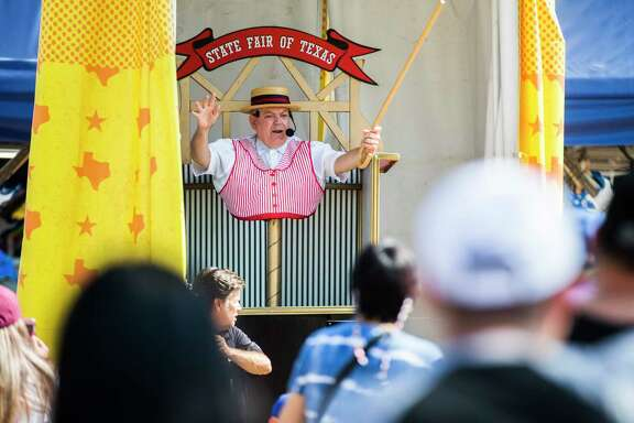 A midway barker greets fairgoers at the State Fair of Texas in October 2019 at Fair Park in Dallas.