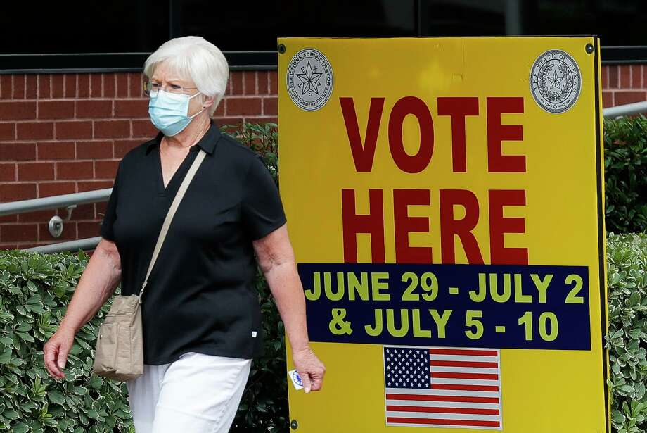 A woman wears a facemask as she walks past a voting sign after voting at the Lee G. Alworth Building during the second day of early voting, Tuesday, June 30, 2020, in Conroe. Early voting for the run-off elections for chief justice of the 9th Court of Appeals, Precinct 2 Constable and judge of the newly created 457th state District Court runs through July 10. Election Day is July 14. The township board of directors election is Tuesday, Nov. 3. Photo: Jason Fochtman, Houston Chronicle / Staff Photographer / 2020 © Houston Chronicle