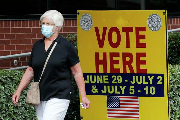 A woman wears a facemask as she walks past a voting sign after voting at the Lee G. Alworth Building during the second day of early voting, Tuesday, June 30, 2020, in Conroe. Early voting for the run-off elections for chief justice of the 9th Court of Appeals, Precinct 2 Constable and judge of the newly created 457th state District Court runs through July 10. Election Day is July 14. The township board of directors election is Tuesday, Nov. 3.