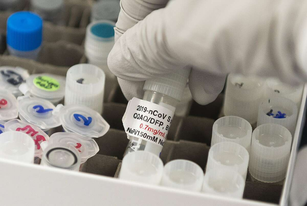 (FILES) In this file photo Dr. Nita Patel, Director of Antibody discovery and Vaccine development, lifts a vial with a potential coronavirus, COVID-19, vaccine at Novavax labs in Gaithersburg, Maryland on March 20, 2020, one of the labs developing a vaccine for the coronavirus, COVID-19. - The US on July 7, 2020 announced it was providing $1.6 billion in funding for the development and manufacture of a COVID-19 vaccine candidate produced by biotech firm Novavax, the largest amount awarded under Operation Warp Speed. Separately, the US also said it was providing $450 million to Regeneron for its experimental COVID-19 treatment and prophylaxis, a combination of two antibodies. (Photo by ANDREW CABALLERO-REYNOLDS / AFP) (Photo by ANDREW CABALLERO-REYNOLDS/AFP via Getty Images)