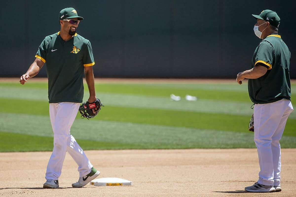 Oakland A's infielder Marcus Semien (left) chats with coach Mike Aldrete during an Oakland A's training camp workout at O.Co Coliseum in Oakland, Calif. Tuesday, July 7, 2020. Due to COVID-19, the 2020 MLB season has been postponed with players just beginning to return for warmups and practices while wearing masks and keeping social distance.