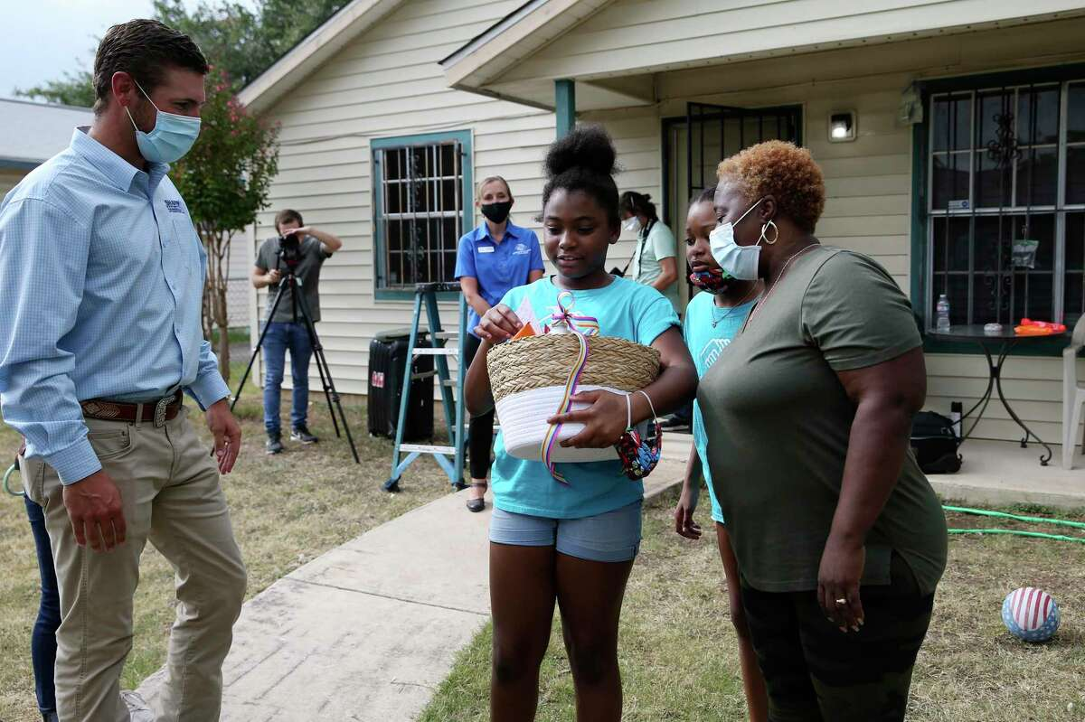 Chase Anderson, owner of Shafer Services Plus, watches as Yolanda Davis and her nieces, Keiaja Davis, 11, second from left and Kandis Davis, 12, check out a gift basket they received from the company and its employees, Tuesday, July 7, 2020. Shafer installed a central AC system at their home through the Boys and Girls Club of San Antonio's Together We Can Campaign. Her nieces attend the East Side Boys and Girls Club.