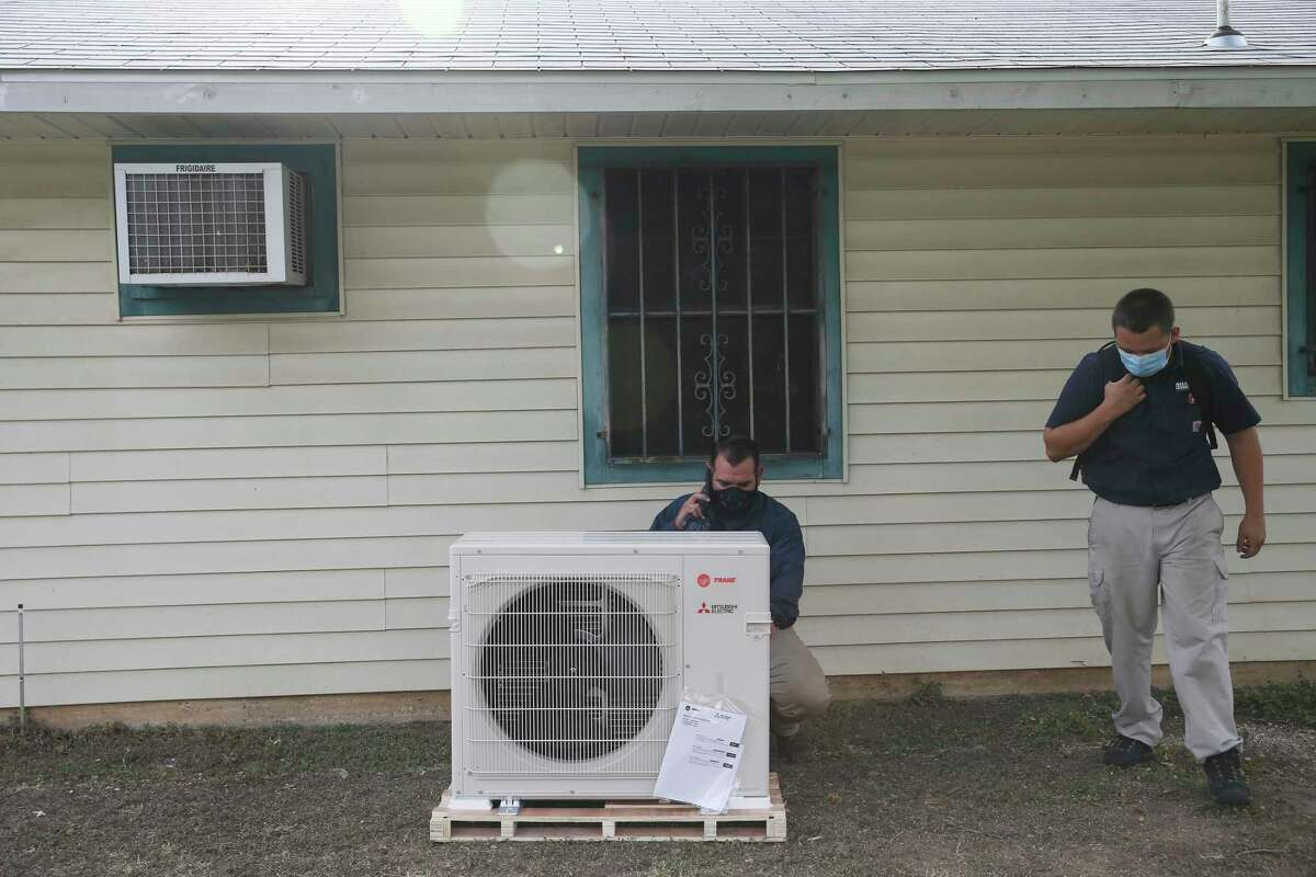 Derek Ramirez, left, and Eric Willitt with Shafer Service Plus work on installing a new AC system at the house of Yolanda Davis, Tuesday, July 7, 2020. The installation was done through the Boys and Girls Club of San Antonio's Together We Can Campaign. Her nieces, who live with her, attend the East Side Boys and Girls Club. Her sons, now adults, also were members of the club.