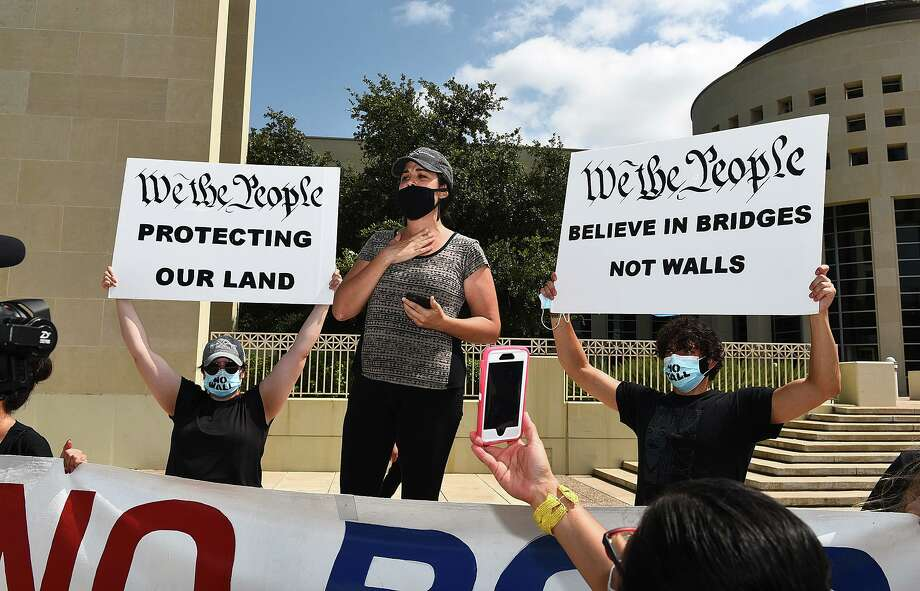 and shoes of those that cannot be present are placed on the ground as the #NoBorderWall Laredo Coalition, which includes residents and land owners, holds a demonstration outside the George P. Kazen Federal Building and United States Courthouse, Tuesday, Jul 7, 2020, to protest the building of a border wall in Laredo. Photo: Danny Zaragoza /Laredo Morning Times