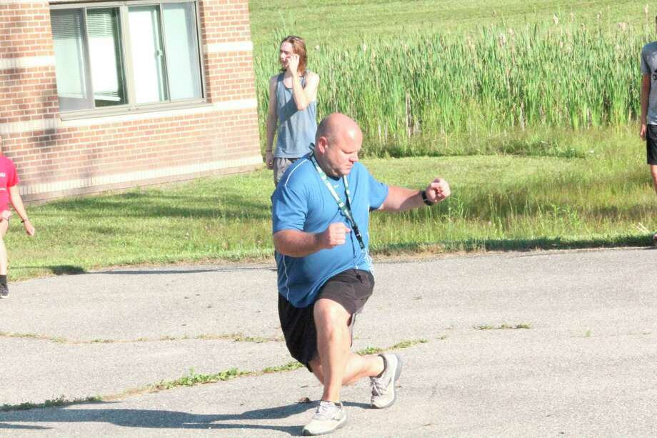 Reed City cross country coach Rich Saladin leads his runners through drills outside the middle school last week. (Herald Review photo/John Raffel)