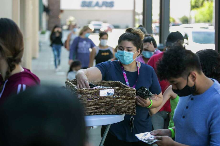 Yessenia Gonzalez, center, selects a free mask near the front entrance of Valley Mall on Tuesday, July 7, 2020, in Union Gap, Wash. The interior portion of the mall reopened Tuesday morning now that Yakima County has entered phase 1.5 of the state's four-phase reopening plan during the coronavirus pandemic. (Amanda Ray/Yakima Herald-Republic via AP) Photo: Amanda Ray, AP / Yakima Herald-Republic