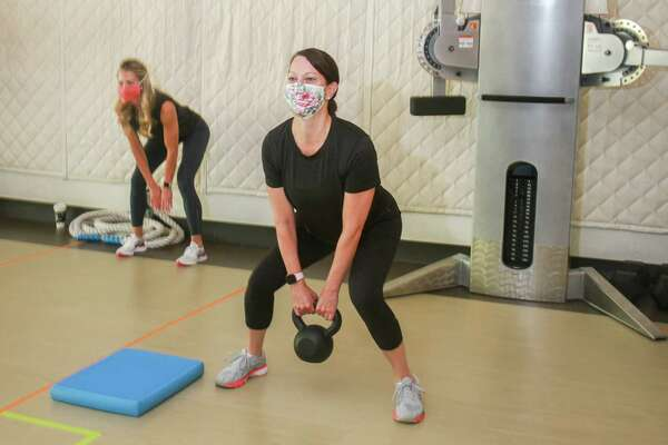 Instructor Cassie Gallagher, left, and Jennifer Girotto during workout at Avenu Fitness in Houston on July 2, 2020. Avenu Fitness has mandated all clients and instructors wear face masks the entire time they're in the facility, including when they're exercising.