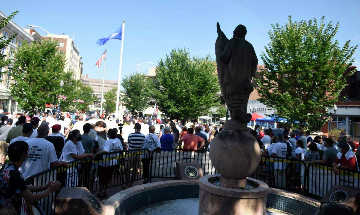 Shadows cover the statue as more than 300 people rally to keep the Christopher Columbus statue in Columbus Park in Stamford, Conn. Sunday, July 5, 2020. UNICO Stamford chapter President Dr. Alfred Fusco spoke to make a point that the Columbus statue in the park should stay.