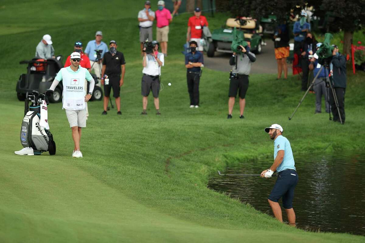 Dustin Johnson of the United States plays a shot as he stands in the water on the 15th hole during the final round of the Travelers Championship at TPC River Highlands on Sunday, June 28, 2020 in Cromwell, Connecticut. (Maddie Meyer/Getty Images/TNS)