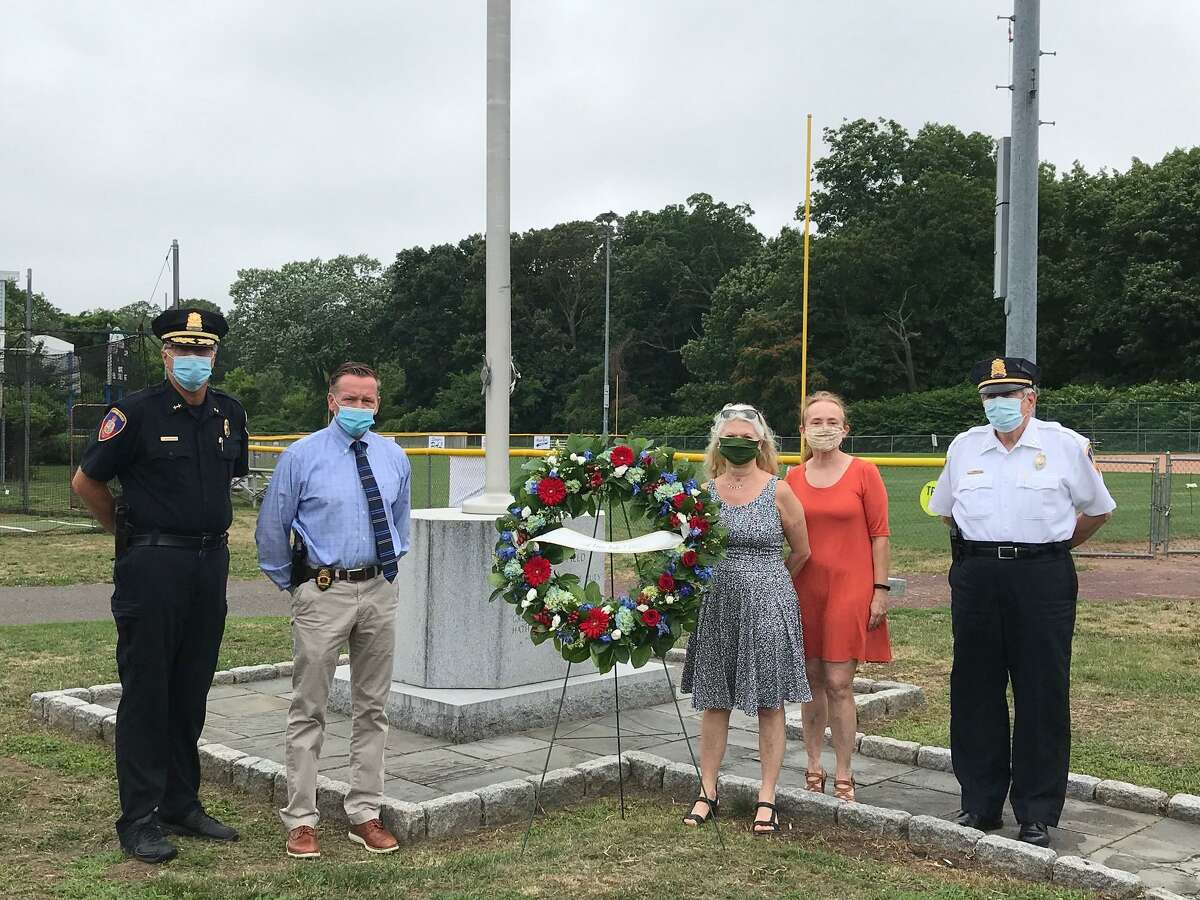 From left: Assistant Police Chief Tom Wuenneman; Police Chief Tim Shaw; late police officer David Troy's daughters, Doreen Dolan and Diane Troy; and Capt. Tom Lombardo stand next to the wreath laid in Troy's memory at Cove Island Park on Tuesday.
