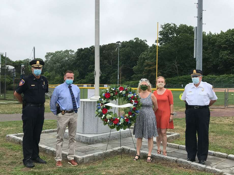 From left: Assistant Police Chief Tom Wuenneman; Police Chief Tim Shaw; late police officer David Troy's daughters, Doreen Dolan and Diane Troy; and Capt. Tom Lombardo stand next to the wreath laid in Troy's memory at Cove Island Park on Tuesday. Photo: Stamford Police Department / Contributed Photo