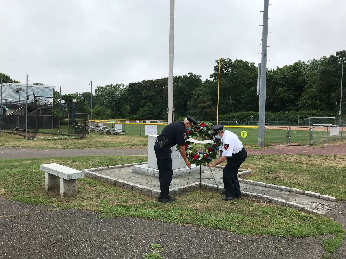 Assistant Police Chief Tom Wuennemann, left, and Capt. Tom Lombardo place a wreath Tuesday at the flag pole dedicated to the memory of police officer David Troy, who was killed in the line of duty during a robbery in Stamford 60 years ago.