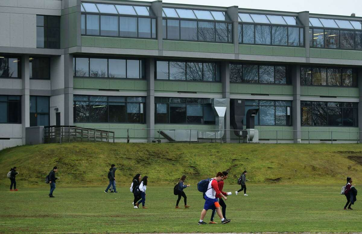 Students exit Norwalk High School after an early dismissal Friday, March 13, 2020, in Norwalk, Conn. The building is now being closed for cleaning until Monday, July 13, 2020 after someone there for summer school tested positive for COVID-19.