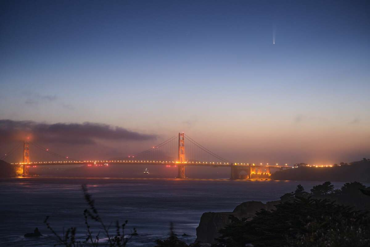 Comet Neowise is viewable by the naked eye in the early morning above the Golden Gate Bridge looking east from San Francisco, Calif. on July 8, 2020.