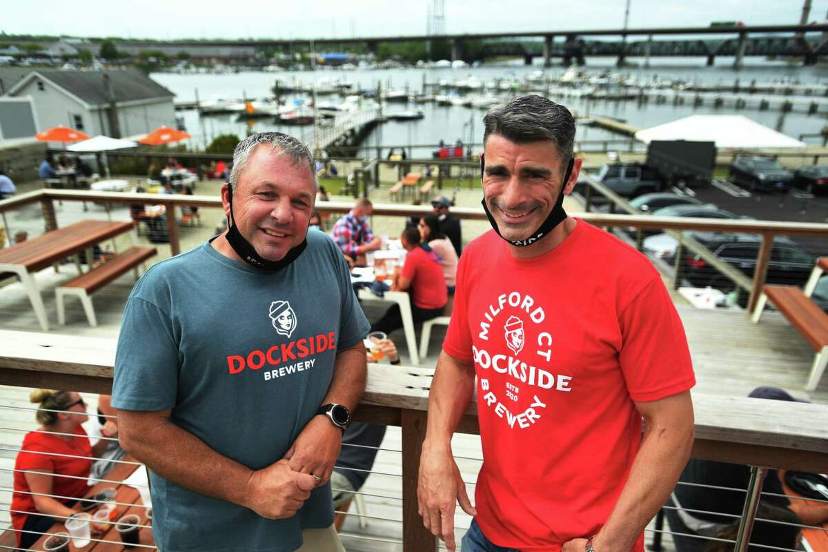 Co-owners Dan Bagley, left, and Bob Chicoine on their multitiered patio overlooking the Housatonic River at the new Dockside Brewery in Milford on May 25.