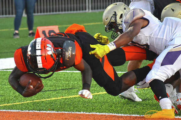 Edwardsville running back Justin Johnson Jr. dives into the end zone for one of his four rushing touchdowns against CBC last season inside the District 7 Sports Complex.