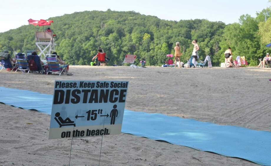 A sign at the town's Martin Park on Great Pond announces a required 15 foot distance between groups on the beach. Photo: Macklin Reid / Hearst Connecticut Media