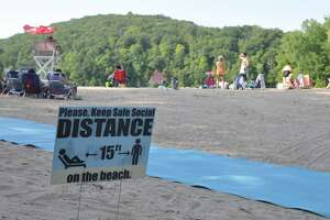 A sign at the town's Martin Park on Great Pond announces a required 15 foot distance between groups on the beach.