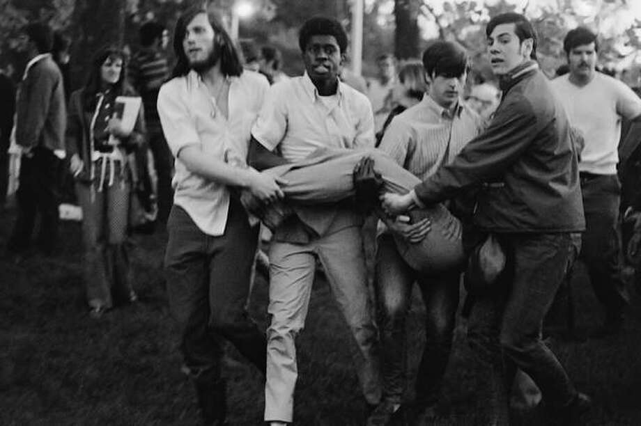 Students carry to safety another student injured in the melee. Photo: John J. Lopinot Photos