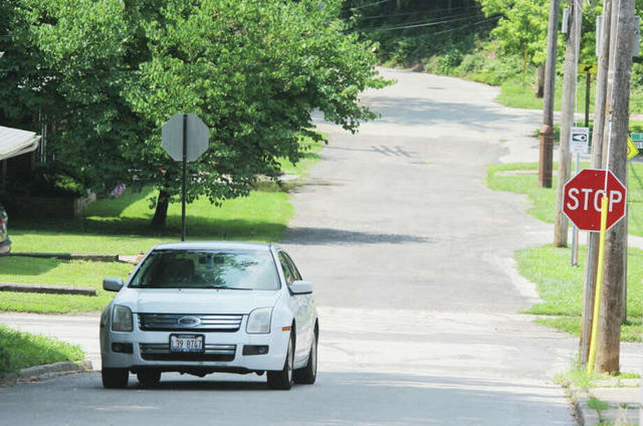A car makes its way along W. Dunn Street towards Main Street in Edwardsville Tuesday. Madison County's Grants Committee approved $100,000 to improve storm water drainage and sanitary sewer systems in its annual Community Development Block Grant program.