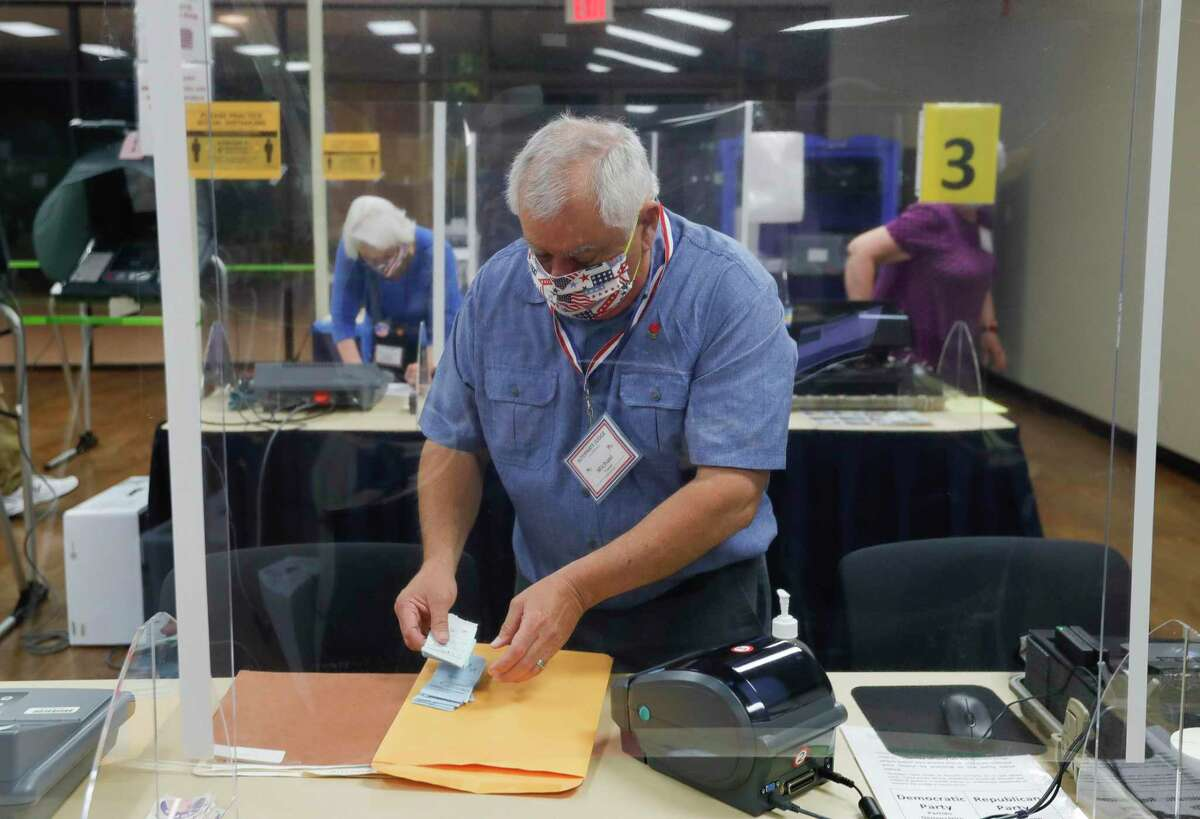 Michael Trahan wears a facemask as he sets up election equipment before the polls open at the South Montgomery County Community Center, Thursday, July 2, 2020, in The Woodlands. Election officials have implemented several safety and sanitization features to protect voters and polling location volunteers from the coronavirus.