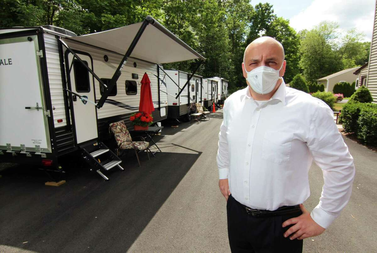 Tyson Belanger, who owns Shady Oaks Assisted Living, poses with some of the trailers he brought in for staff to live in at the facility in Bristol, Conn., on Thursday June 18, 2020. In March as the coronavirus spread through the state Belanger established a bubble at his facility, paying staff at great personal expense to stay full time at the residency.