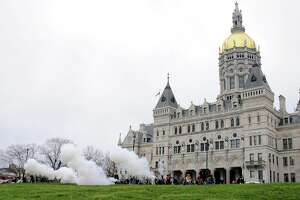 Period cannons fired by war enactors outside the Connecticut State Capitol in April 2011 to commemorate the Civil War's 150th anniversary. The Capitol building, erected in 1878 to celebrate the war, includes statues of state heroes on the campus and around the third-floor facade of the exterior.