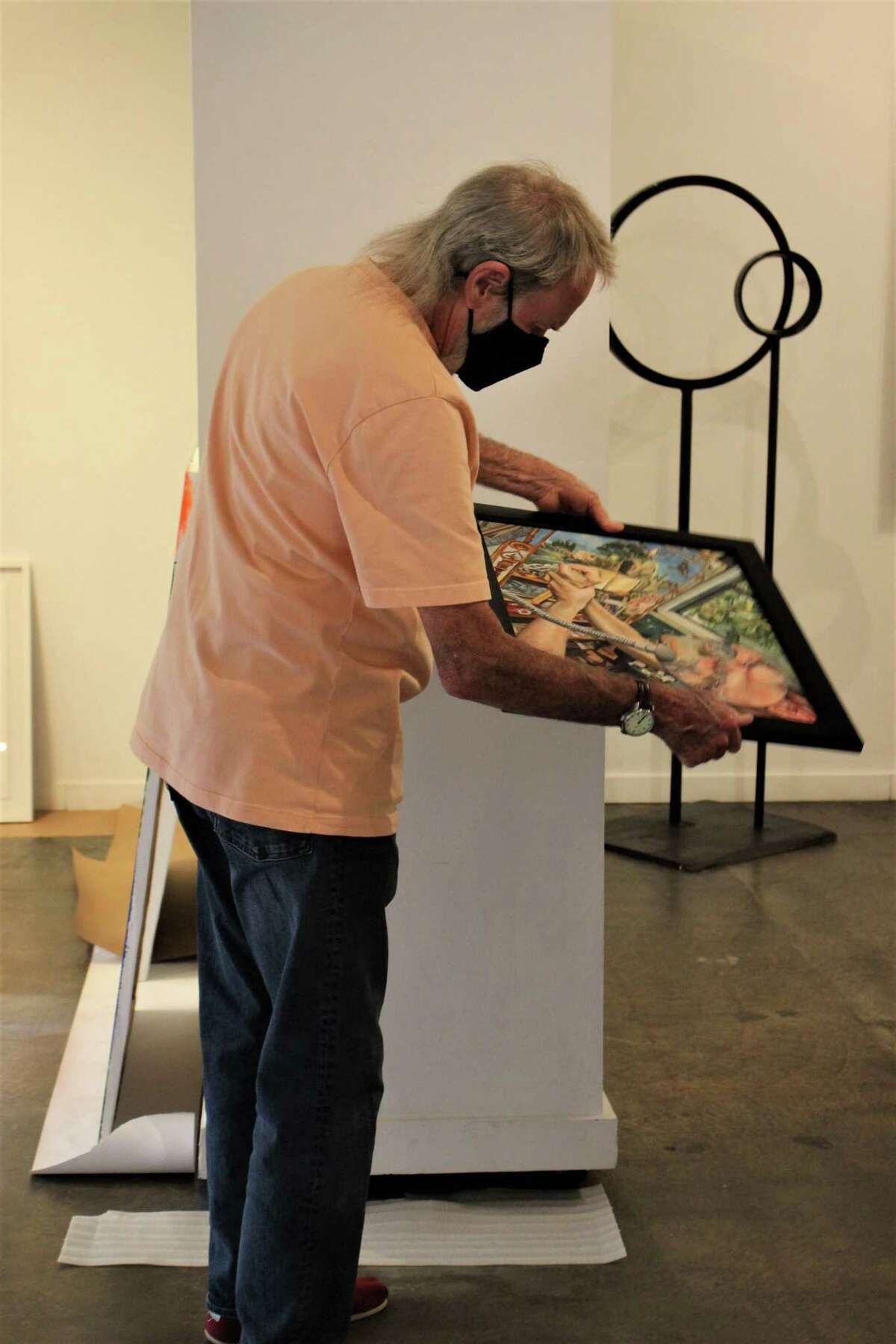Selected juror Wayne Gilbert studies a piece of art from Archway Gallery's 12th Annual Juried Exhibition. A Facebook Live watch party on Sunday, July 5, announced 39 works selected for the show from 243 submissions.