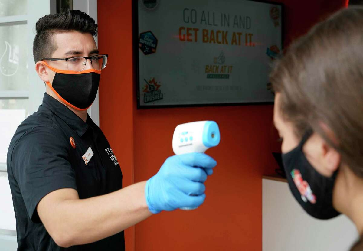 Josue Garcilazo, studio manager, left, demostrates with Megan Gill, public relations representative, right, how temperatures of members are taken outside before they enter Orangetheory Fitness Highland Village, 2400 Mid Lane, shown Tuesday, July 7, 2020, in Houston.
