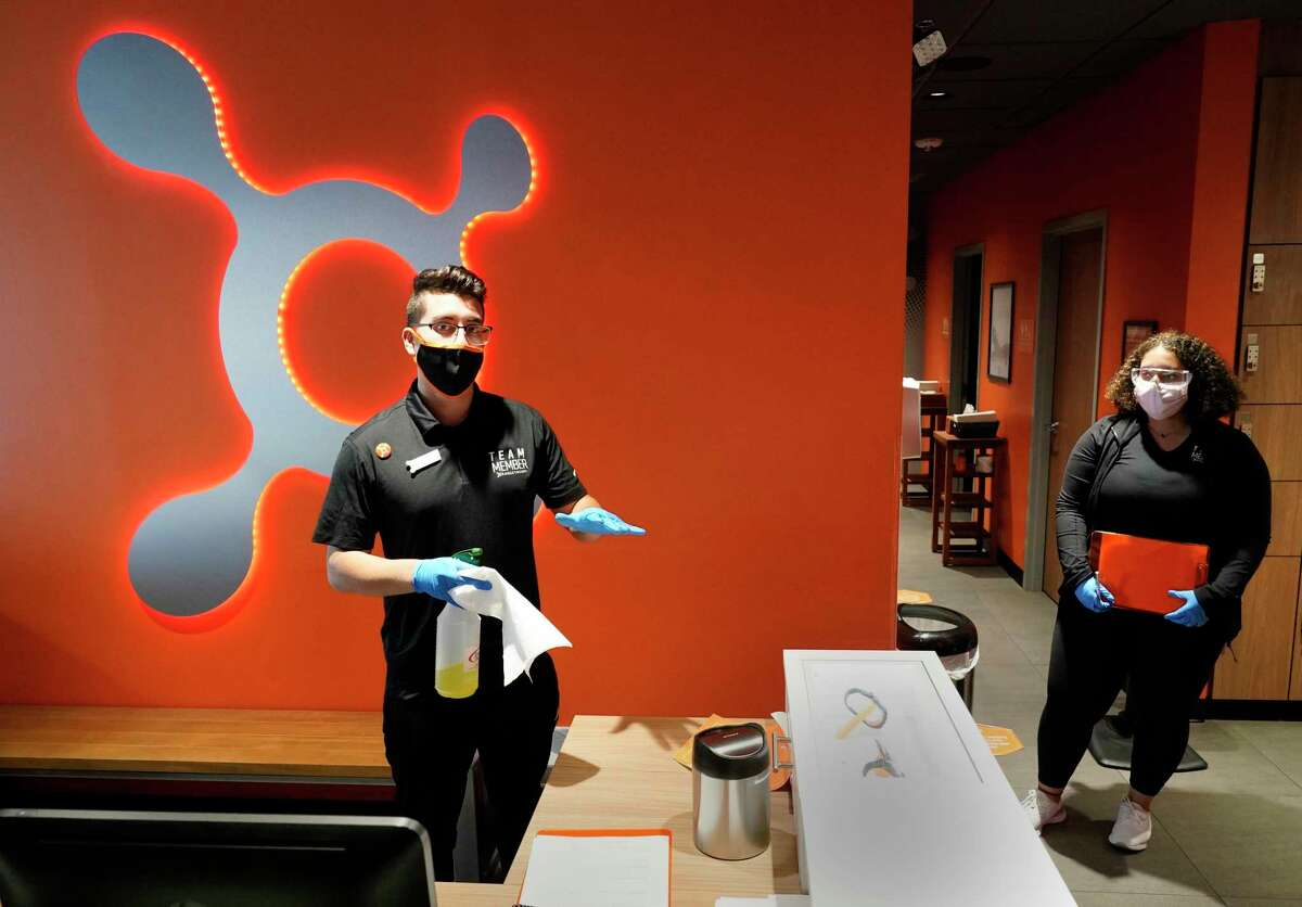 Josue Garcilazo, studio manager, left, along with Lessly Cordero, sales associate, right, talks about the cleaning procedures at Orangetheory Fitness Highland Village, 2400 Mid Lane, shown Tuesday, July 7, 2020, in Houston.