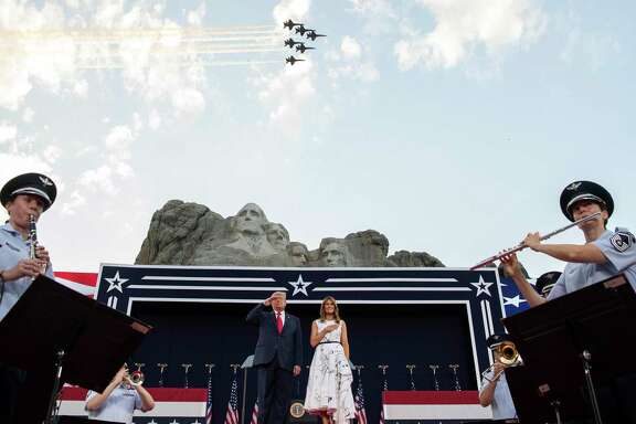 President Donald Trump, accompanied by first lady Melania Trump, stands during the national anthem with a flyover by the U.S. Navy Blue Angles at Mount Rushmore National Memorial, Friday, July 3, near Keystone, S.D.  A reader thinks it's peculiar how the president allows his followers to not wear masks or practice social distancing while he keeps a healthy distance.