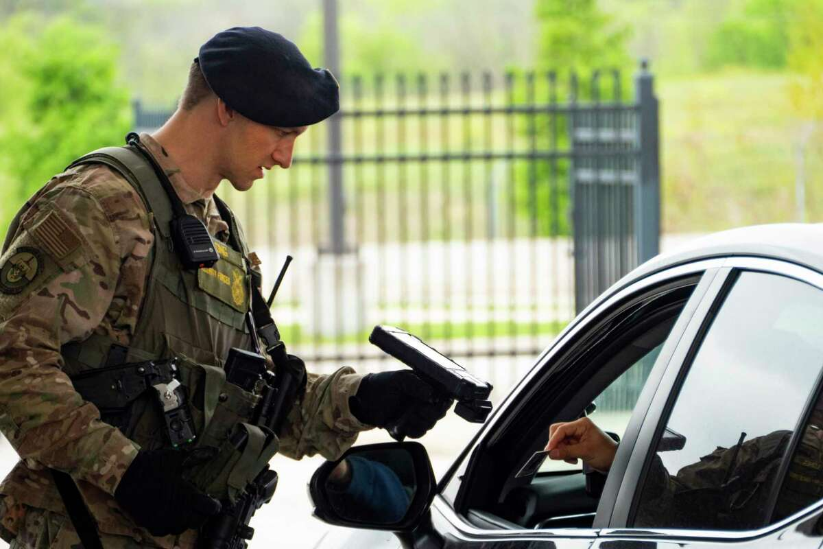 Air Force Staff Sgt. James Long checks traffic at the main gate to enter JBSA-Brooke Army Medical Center in March, as the pandemic tightened access to the hospital.