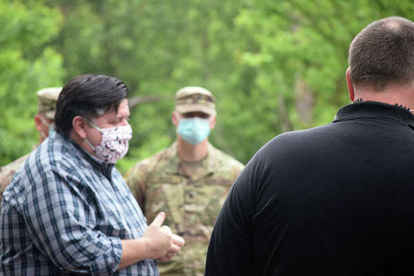 Gov. J.B. Pritzker takes to emergency officials in May as they survey flooding in Meredosia.