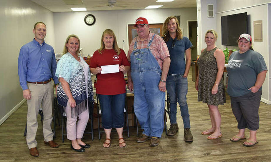 Farmers State Bank vice presidents Bryan Hubbert (from left) and Nichole Mason present a donation to Outreach Community Center representatives Marsha Mayner, Kenny Mayner Sr., Kenny Mayner, Mysti Dahman and Andie Fundel. Photo: Photo Provided