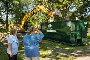 Penny Tyler, right, and longtime friend Mary Foster, left, look out across the lawn as Tyler's childhood home in Sanford is demolished Wednesday, July 8, 2020 in preparation for a new home to be built free of cost thanks to Great Lakes Homes in Freeland. The Islamic Center of Midland and Midland Area Interfaith Friends will furnish the home. (Katy Kildee/kkildee@mdn.net)