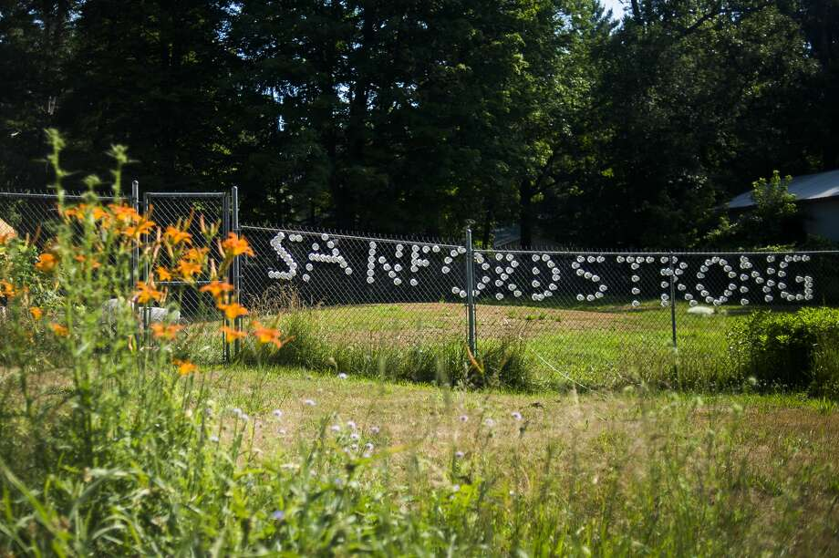 """""""Sanford Strong"""" is spelled out along a fence across the street from Penny Tyler, whose childhood home was demolished earlier Wednesday, July 8, 2020 in preparation for a new home to be built free of cost thanks to Great Lakes Homes in Freeland. (Katy Kildee/kkildee@mdn.net) Photo: (Katy Kildee/kkildee@mdn.net)"""