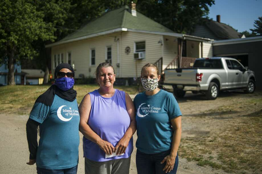Umbareen Jamil, left, and Haley Lodhi, right, of the Islamic Center of Midland, pose for a photo Wednesday with Sanford resident Lori Brown, center, after Brown received a check for $500 from Reliable Plumbing and Heating to help fix her furnace, which was damaged in the flood. The business was too busy to help her, so they offered financial support. Brown lives across the street from Penny Tyler, whose childhood home was demolished earlier Wednesday, July 8, 2020 in preparation for a new home to be built free of cost thanks to Great Lakes Homes in Freeland. The Islamic Center of Midland and Midland Area Interfaith Friends will furnish the home. (Katy Kildee/kkildee@mdn.net) Photo: (Katy Kildee/kkildee@mdn.net)