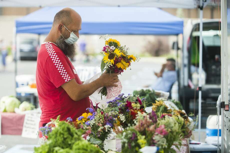 Customers peruse stalls at the Midland Area Farmers Market Wednesday, July 8, 2020 at its temporary location in the large parking lot next to Dow Diamond. (Katy Kildee/kkildee@mdn.net) Photo: (Katy Kildee/kkildee@mdn.net)
