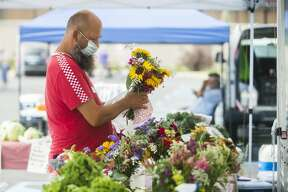 Customers peruse stalls at the Midland Area Farmers Market Wednesday, July 8, 2020 at its temporary location in the large parking lot next to Dow Diamond. (Katy Kildee/kkildee@mdn.net)