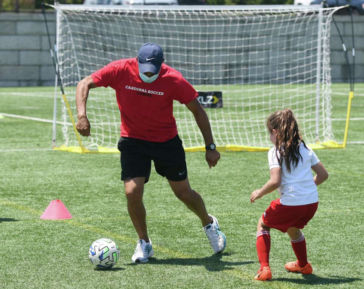 Soccer coach Fabricio Silva runs a drill during the Cardinal Soccer Camps at Cos Cob Park in the Cos Cob section of Greenwich, Conn. Monday, July 6, 2020. The town opened playing fields and basketball courts to use this week after months of closure due to the coronavirus.