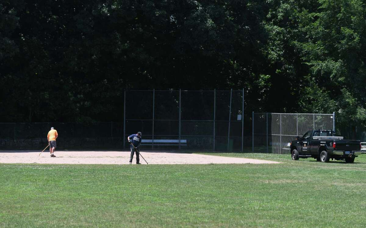 City workers maintain the baseball field at the Bible Street Playground in the Cos Cob section of Greenwich, Connecticut on Monday, July 6, 2020. The city has opened playing fields and basketball courts in use this week after months of closure due to coronavirus.