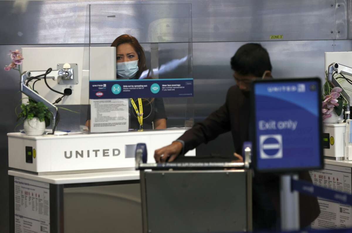 A United Airlines worker helps a customer at San Francisco International Airport on July 08, 2020 in San Francisco, California. As the coronavirus COVID-19 pandemic continues, United Airlines has sent layoff warnings to 36,000 of its front line employees to give them a 60 day notice that furloughs or pay cuts could occur after October 1.