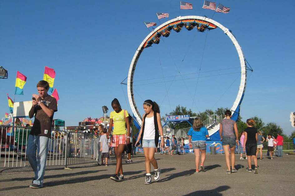 Youths stroll in front of the Fireball carnival ride on the midway in advance of the Texas Rice Festival in Winnie.